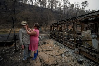 Mark Brooks is comforted by his daughter Kylee on January 9, after returning to the remains of his home near Corryong.