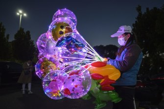 A woman wears a protective mask as she sells balloons outside a local shopping centre in Beijing, China.