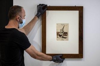 A Goya drawing being hung at the NGV.