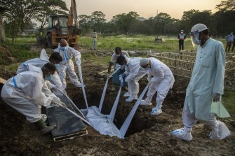 Relatives and municipal workers in protective suits bury the body of a COVID-19 victim in Gauhati, India.