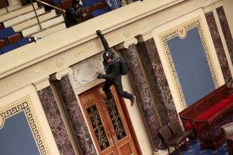 Seorang perusuh tergantung dari balkon di ruang Senat.