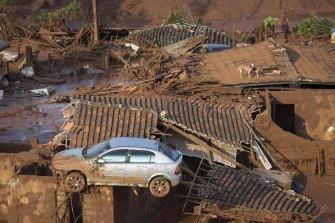 A car and two dogs are seen on the roof of destroyed houses in the small town of Bento Rodrigues, Brazil, after the Samarco dam collapse in 2015.