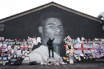 Street artist Akse P19 repairs the defaced mural of Manchester United striker and England player Marcus Rashford.