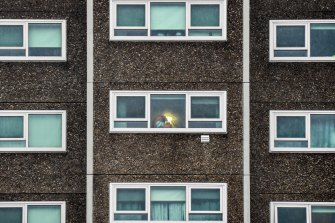 A woman is seen looking out her apartment window at a North Melbourne public housing tower on July 5 during a hard lockdown.