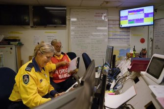 NSW RFS air ops manager Peter Windle (right) and aviation radio operator Danielle Brice (left) working in the operations room at the Eurobodalla operations fire control centre in Moruya.