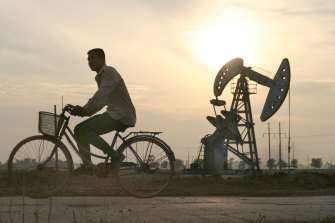 A cyclist passes by oil wells at sunset at Sinopec's Shengli Oil Field in China's Shandong Province June 26, 2003. Oil refiners and traders in Asia may have shipped as much as 500,000 metric tons of gasoil, or diesel, in a month to South America and the U.S., where rising demand for the fuel is helping to sap excess supplies from the Asian region. Photographer: Kevin Lee / Bloomberg News man on bike / bicycle