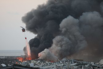 A helicopter drops water following the large explosion at the Port of Beirut in Beirut, Lebanon, on August 4.