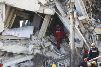 Rescuers search for people buried under the rubble at a collapsed building in Elazig, eastern Turkey on Saturday.