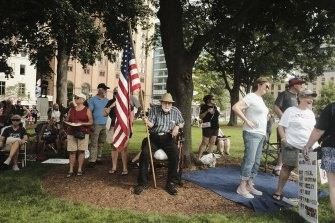 A demonstrator holds an American flag during a protest against COVID-19 vaccination mandates in Lansing, Michigan, on Friday, August 6, 2021.