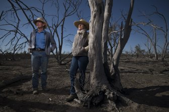 Angus beef producers Garry and Leanne Hall view dead red river gums near a dry Macquarie River at their property in the Macquarie Marshes in August 2019.