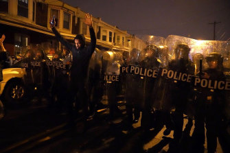 A man raises his arms in front of the police line during a protest in response to the police shooting of Walter Wallace.
