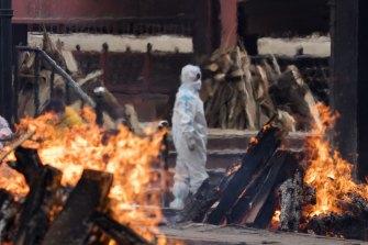 A man at a crematorium in New Delhi farewells a relative who died of COVID-19.