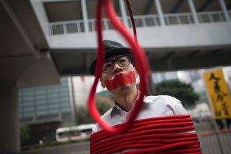 "A protester stands in front of a noose that reads: ""Kidnapping"" during a protest against the disappearance of five booksellers in Hong Kong in 2016."