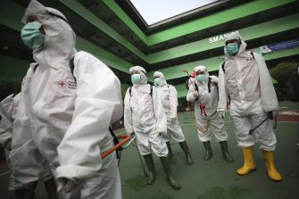 Members of Indonesian Red Cross prepare to disinfect a school in the wake of coronavirus outbreak in Jakarta.