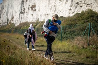 A migrant family walks along the coast  in Deal, England, on September 15. More than 6100 migrants have made the Channel crossing by boat this year according to an analysis by the Press Association.