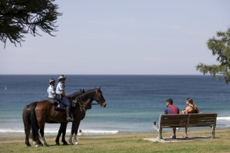 Mounted police at Bondi Beach question beachgoers on April 3.