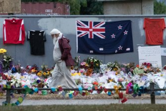 A Muslim man walks past a makeshift memorial on the walls surrounding the al-Noor Mosque.