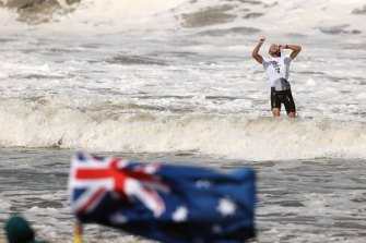 Owen Wright takes a moment in the surf to let his bronze medal sink in as an Australian flag flutters in the foreground.