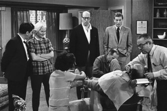 Standing, Morey Amsterdam (left), Rose Marie, Richard Deacon and Dick Van Dyke, right, watch Carl Reiner, in barber chair, during a rehearsal for the The Dick Van Dyke Show in 1963.