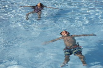 Hugo Akar, 5, and his sister Milani, 6, float at Crawford Pool in Shaler, Pennsylvania. The public pool was one of the first in the region to reopen after COVID restrictions.