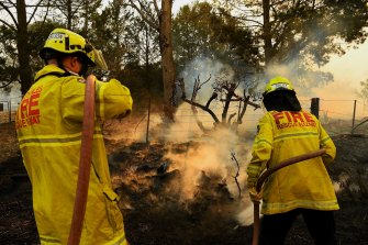 Firefighters hose down  the terrain after extinguishing flames near Bargo.