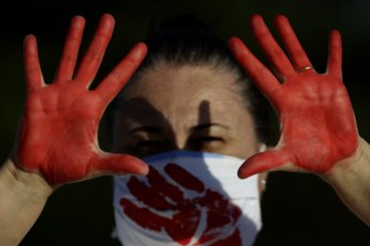 A demonstrator shows her red-painted hands representing the blood of the more than 216,000 deaths from the COVID-19 pandemic in Brazil, during a protest against the government's response in Brasilia on Sunday.