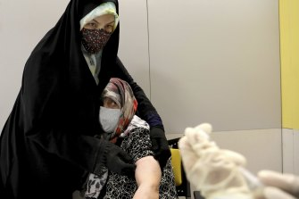 An Iranian woman receives a Sinopharm vaccine for COVID-19 at a shopping centre in Tehran.