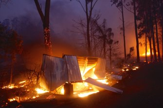 Photographs shows burning properties in Rainbow Flat on Friday night after fire from the Hillville Fire broke containment lines.