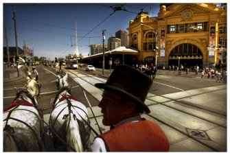 A horse-drawn carriage passes Flinders Street Station.
