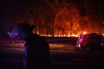 A RFS fire fighter with the Charmhaven unit monitors a small flare up on New Years Day.