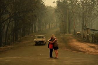 Residents comfort each other on Runniford Road in Nelligen where several homes and out buildings were destroyed or damaged in the fire near Batemans Bay.