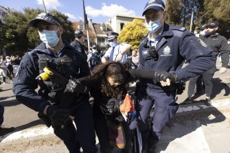Police arrest a woman on Broadway during the Sydney rally on Saturday.