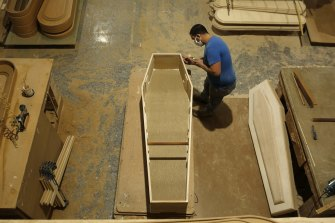 An employee works with a coffin at the Adean coffin-making factory in Spain.