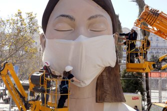 Workers place a mask on the figure of the Fallas festival in Valencia.