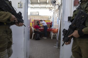 Israeli soldiers stand guard as a Palestinian who works in Israel receives a Moderna COVID-19 vaccine at the Tarqumiya crossing between the West Bank and Israel.