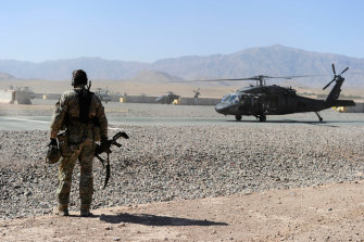 An SAS soldier awaits the arrival of a UH-60 Blackhawk helicopter in Afghanistan.