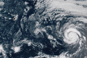 Hurricane Douglas, right, churning in the Pacific Ocean heading towards Hawaii, left. The storm is currently a Category 3 hurricane but is expected to weaken before it arrives in the state on Sunday.