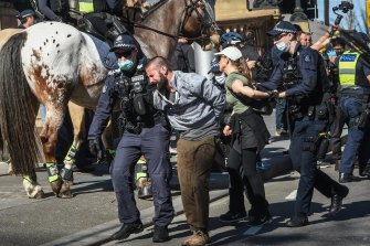 Police and protesters clash on Spring Street during Saturday's anti-lockdown rally.