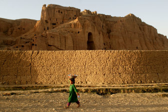A girl in Bamiyan, Afghanistan passes the void where a giant 6th-century statue of Buddha stood before its destruction by the Taliban. Countless items of the region's heritage have been destroyed or smuggled out during decades of conflict.