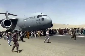 People run alongside a US Air Force transport plane as it moves down a runway of the international airport in Kabul.