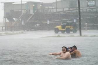 The relative calm before the storm: People play in a flooded parking lot at Navarre Beach in Florida.