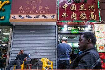 Men sit in front of a restaurant off Little North Road, part of an ethnically diverse quarter in Guangzhou known as Little Africa.