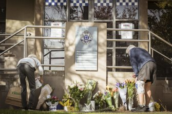 Flowers are placed at a makeshift memorial at Boroondara Police Station in memory of the officers killed.