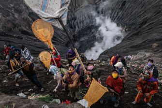 Villagers use nets to catch offerings thrown by Tenggerese worshippers during the Yadnya Kasada Festival at crater of Mount Bromo amid the coronavirus pandemic.