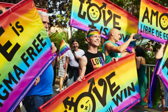 Attendees hold signs during a Stonewall Inn 50th anniversary commemoration rally in New York in June during WorldPride.
