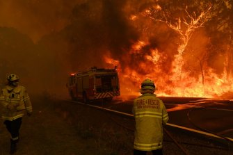 Fire and Rescue NSW escape flames as the Gospers Mountain fire crosses the Bells Line of Rd at Berambing.