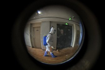 Seen through a door peephole, a medical worker wearing a protective clothing disinfects the corridor of a hotel used for foreigners to stay during a period of health quarantine in Shanghai in August.