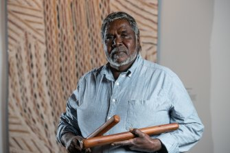 Artist Djambawa Marawili AM from Yilpara, NT, in front of his artwork Journey to America.