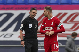 Jordan Henderson speaks to referee Michael Oliver as they wait for the VAR decision that would rule out Henderson's winner.