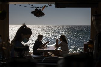 People sit on a terrace at a beach in Barcelona, Spain. Eased lockdown measures in some areas allow social gatherings in limited numbers, restaurant and bar service with outdoor sitting.